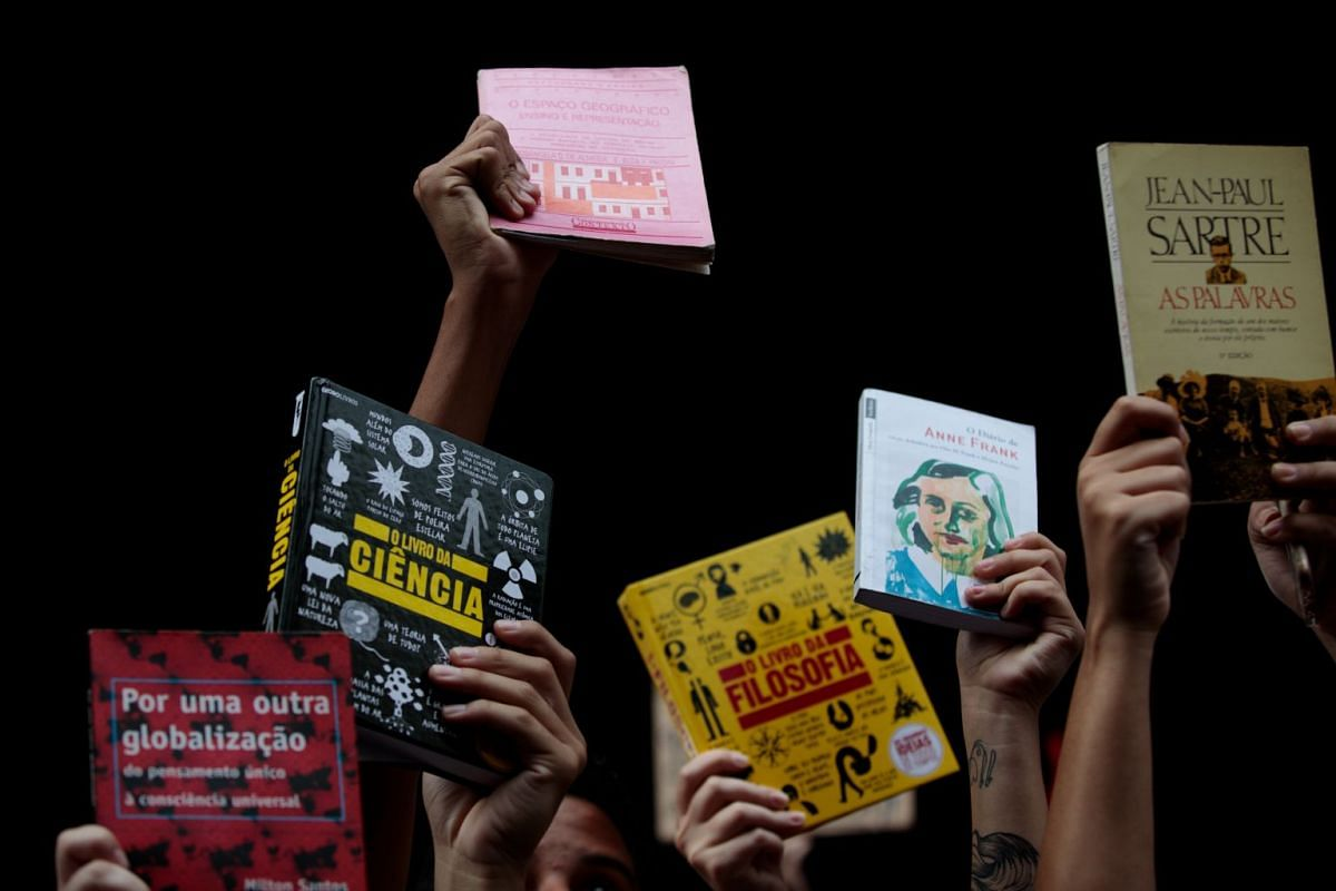 """Demonstrators hold up books on Paulista Avenue during a protest with the slogan """"Books Yes, Weapons No"""" in Sao Paulo on May 15, 2019."""