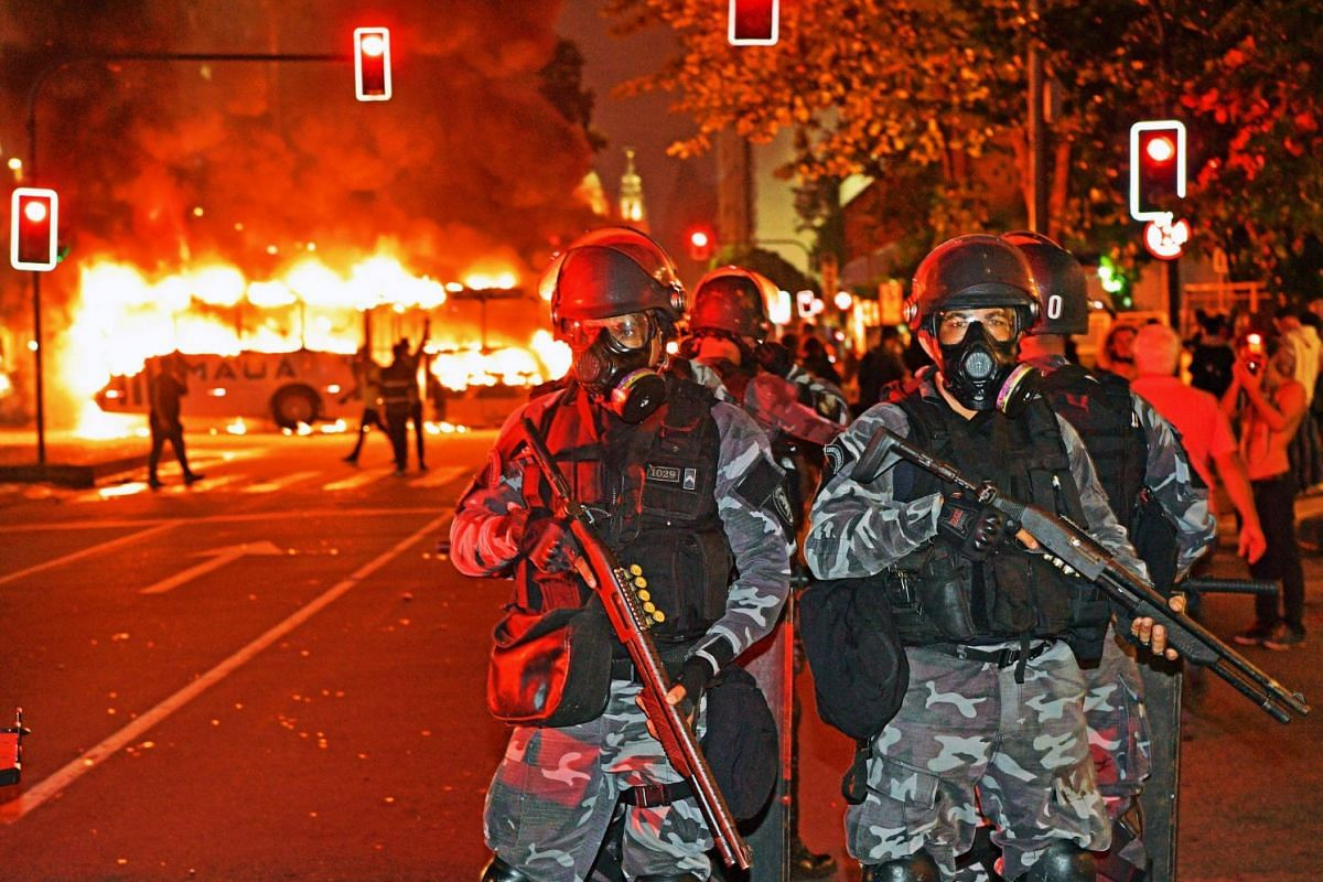 Officers of a special unit of the military police are deployed near a bus in flames during a protest in Rio de Janeiro on May 15, 2019.