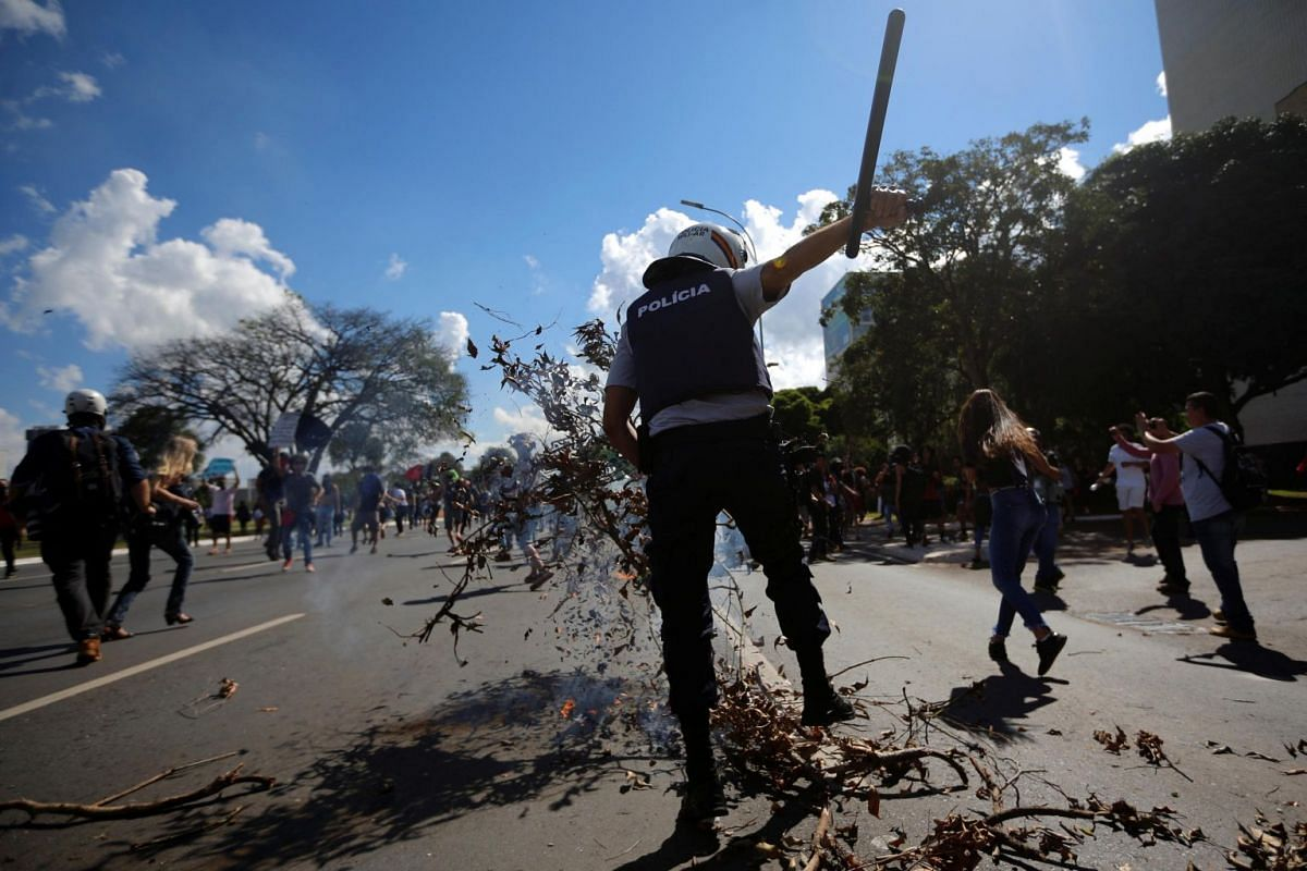 Riot police and university students clash during a protest in Brasilia on May 15, 2019.