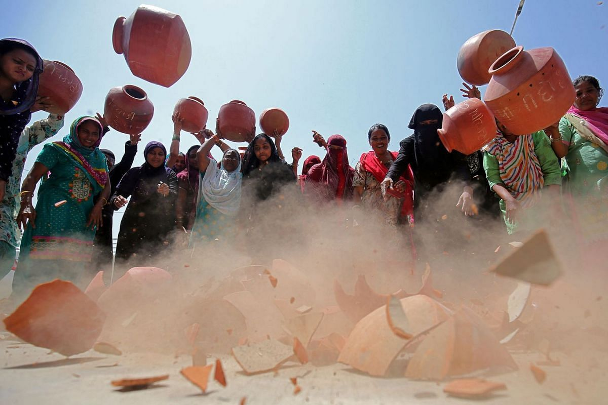 Women throw earthen pitchers onto the ground in protest against the shortage of drinking water outside the municipal corporation office in Ahmedabad, India, May 16, 2019. PHOTO: REUTERS