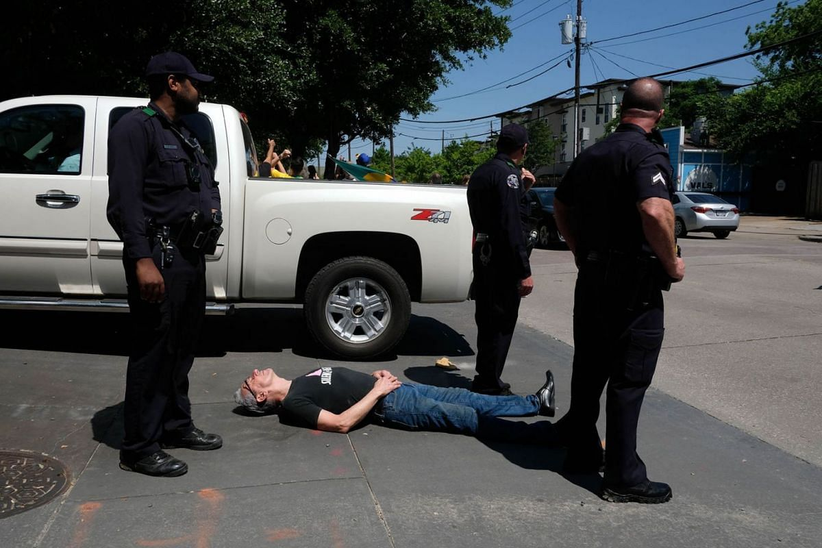 """Gary Bellomy, a longtime Dallas activist, lies in the driveway of the Old Parkland complex in downtown Dallas, Texas, on May 16, 2019, where the Brazilian president was scheduled to receive a """"person of the year"""" award from the Brazilian-American Cha"""