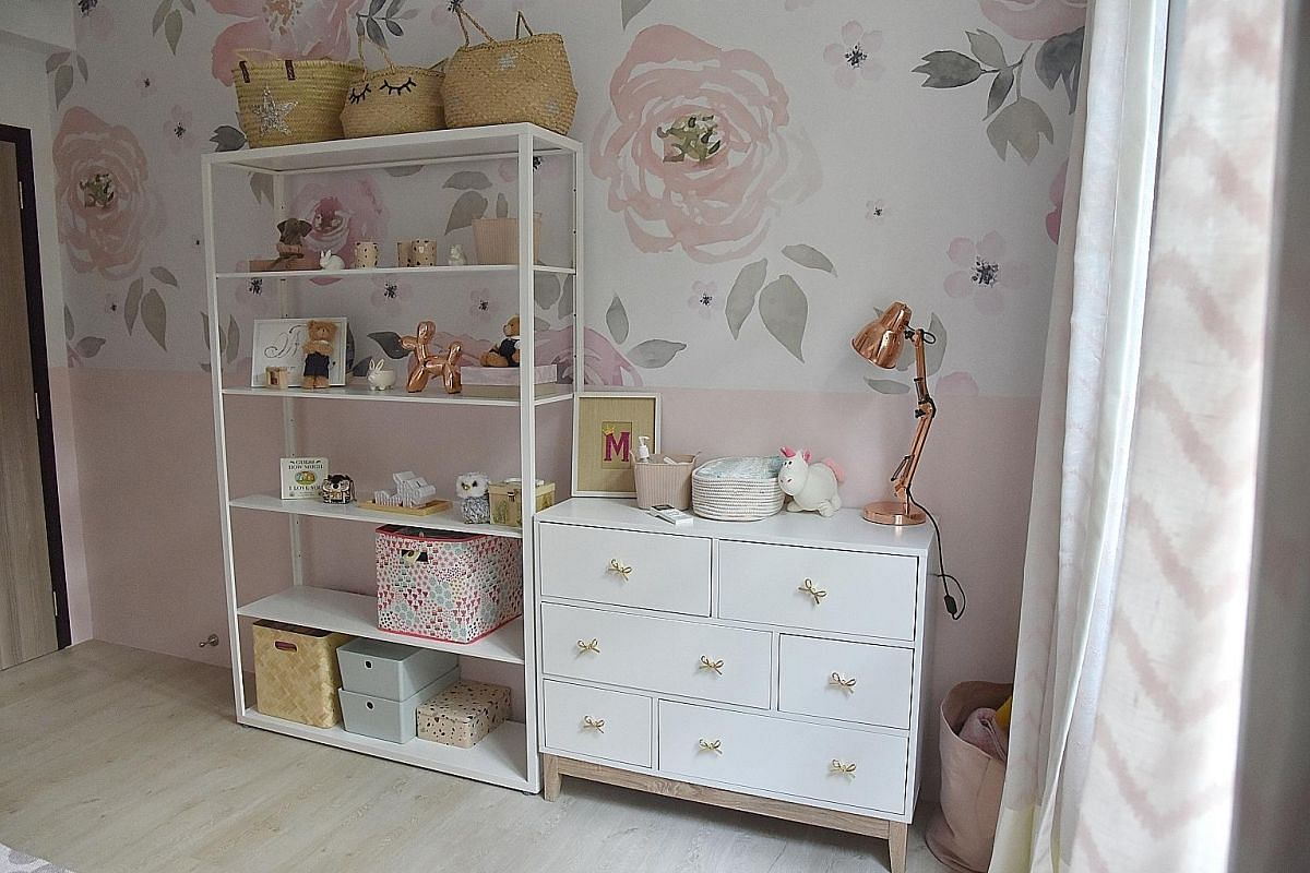 The room belonging to Ms Goh's daughter has a more girlish vibe, with half a wall of floral wallpaper and a mostly pink palette.