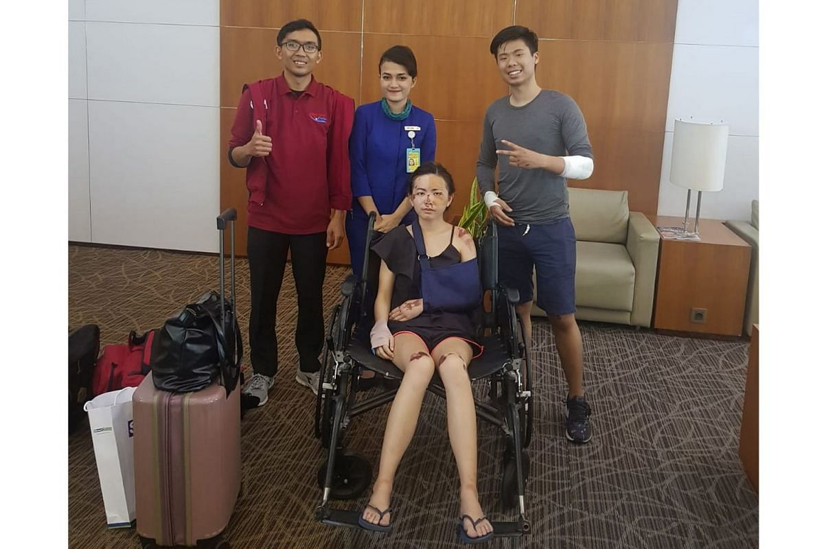 Married Singapore couple Eugene Aathar (far right) and Dolly Ho (seated) were riding a rented scooter in Kuta, Bali, on May 6 when they were robbed, injured and harassed. Staff from the airport (in blue) and MediVac Asia (in red) escorted them at the Ngur