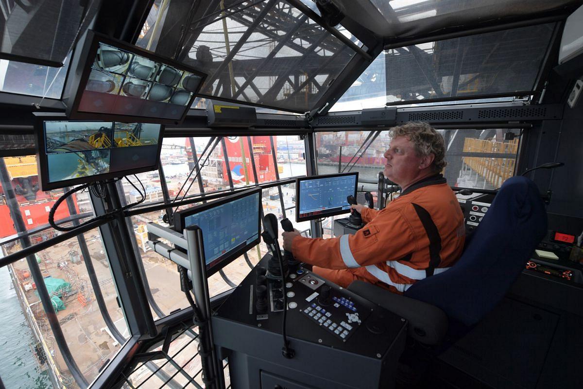 Crane operator Johan Schonenberg in the crane cabin control room piloting one of the tub-mounted heavy lift cranes.