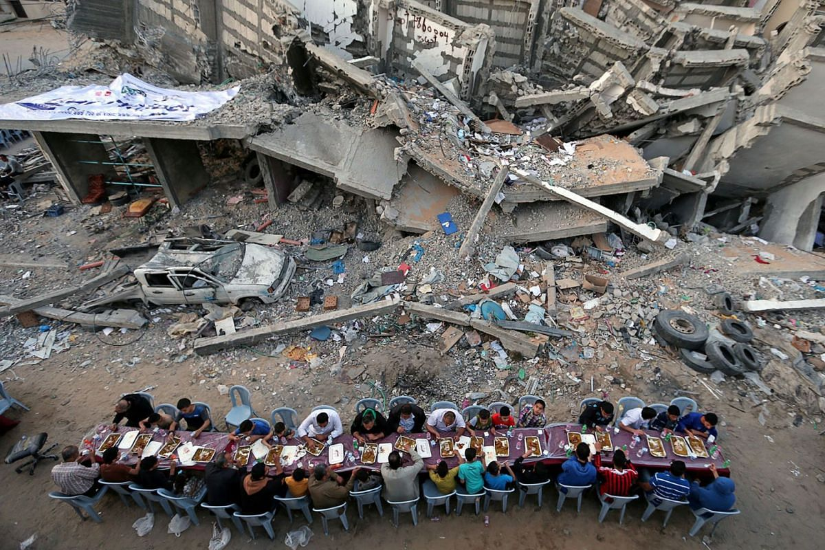 Palestinians break their fast by eating the Iftar meals during the holy month of Ramadan, near the rubble of a building recently destroyed by Israeli air strikes, in Gaza City May 18, 2019. PHOTO: REUTERS