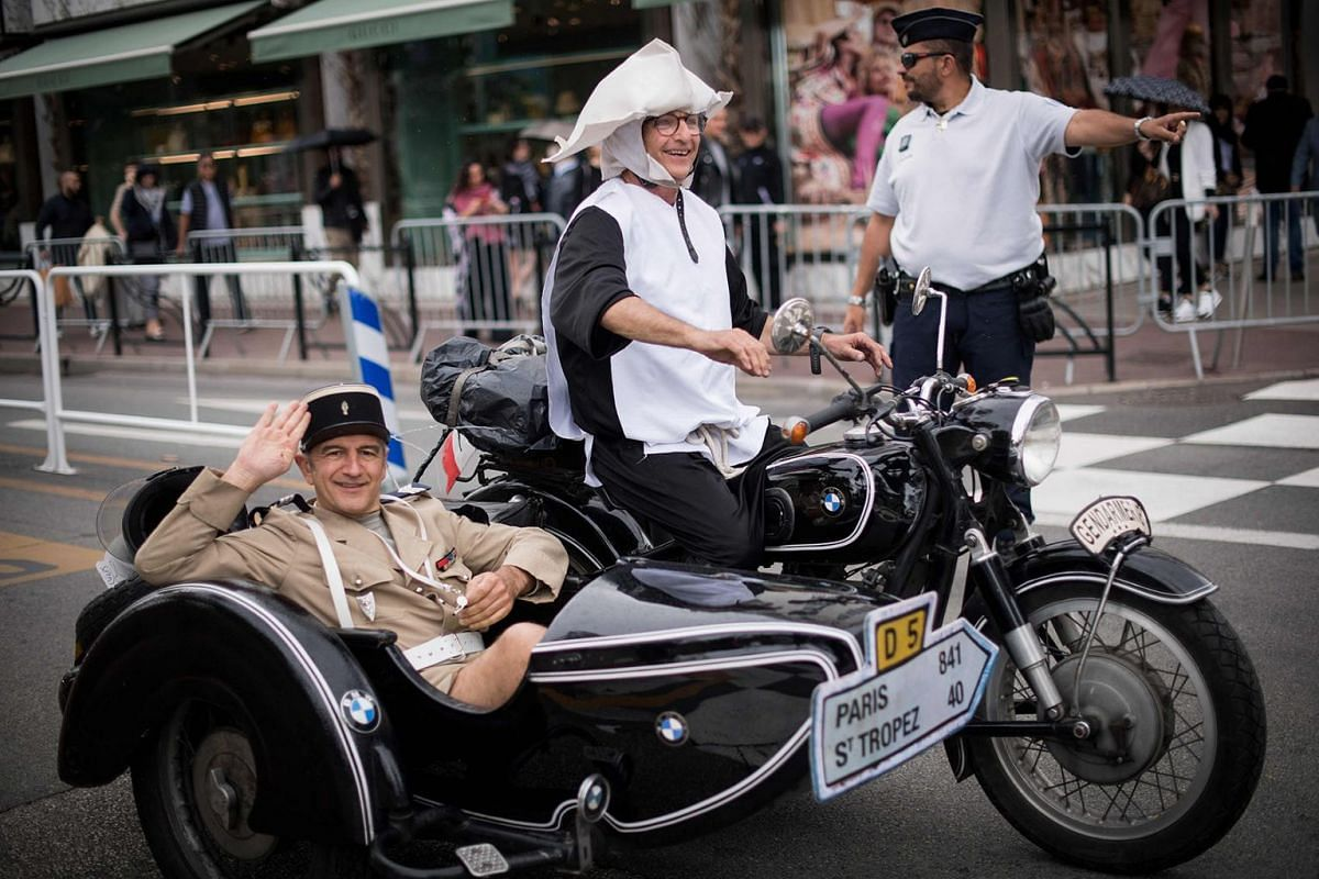 "Performers dressed as characters from the 1964 French comedy ""The Troops of St. Tropez"" (Le Gendarme de Saint-Tropez) drive on the Promenade de la Croisette during the 72nd edition of the Cannes Film Festival in Cannes, southern France, on May 19, 20"