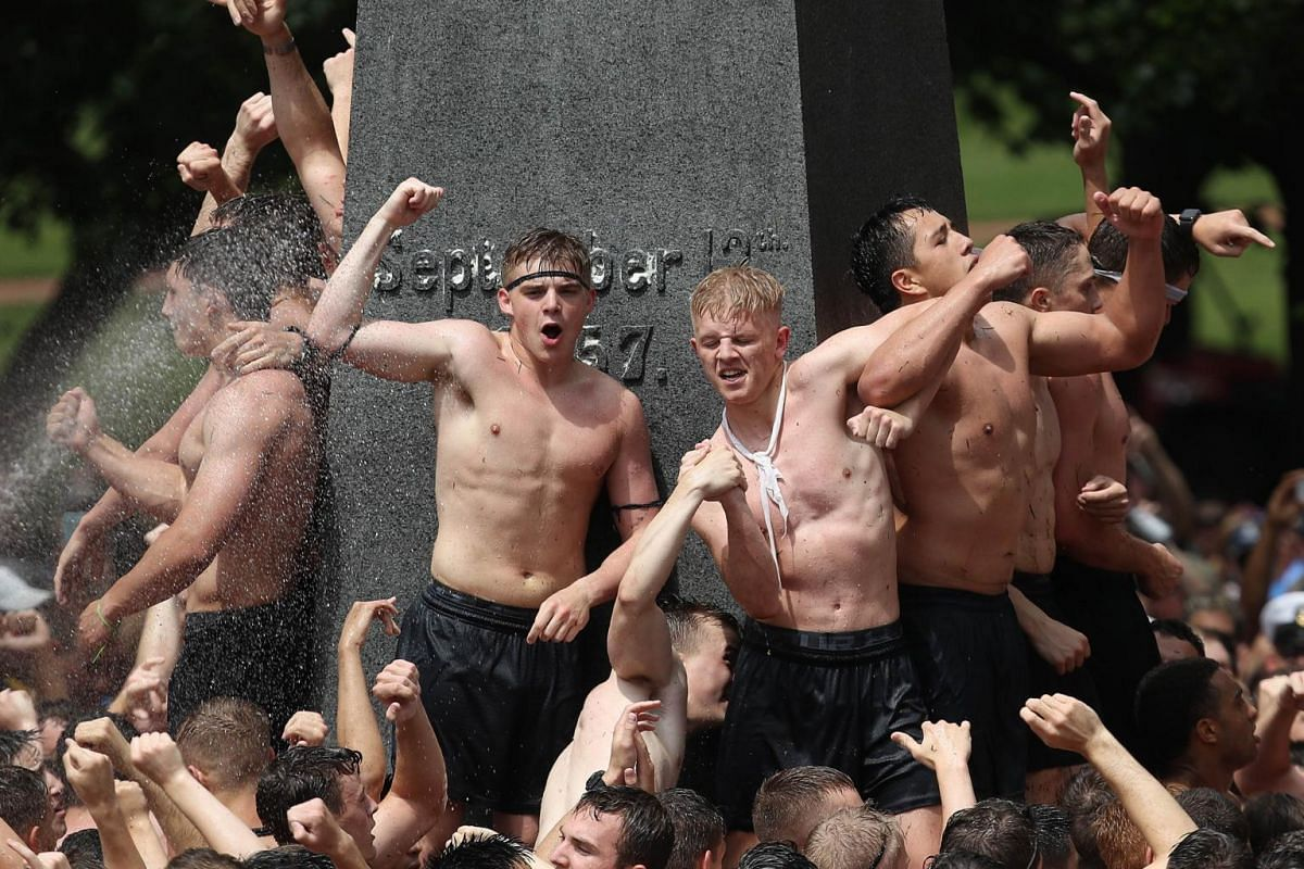 After more than an hour's worth of work, the 2022 plebe class from the US Naval Academy celebrates after successfully placing an upperclassman's hat atop the Herndon Monument in the annual tradition in Annapolis, Maryland, on May 20, 2019.