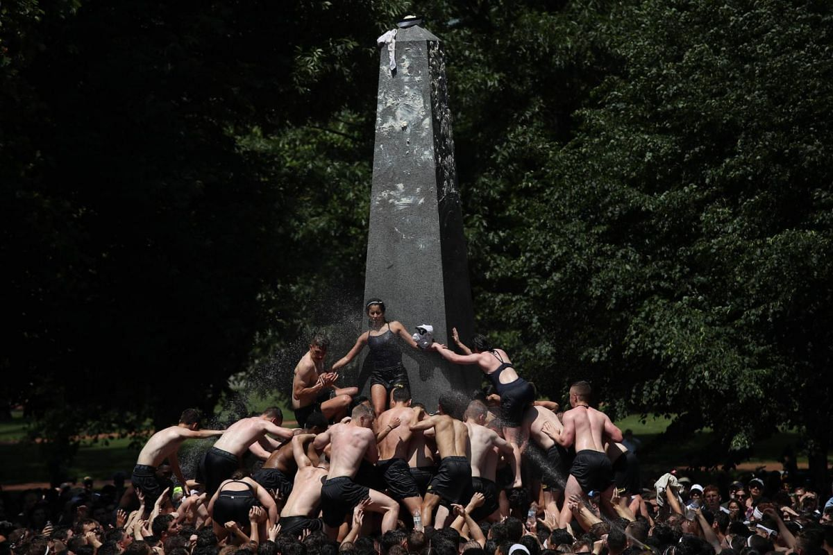 The 2022 plebe class from the US Naval Academy works to scale the Herndon Monument and place an upperclassman's hat atop the monument in the annual tradition in Annapolis, Maryland, on May 20, 2019.