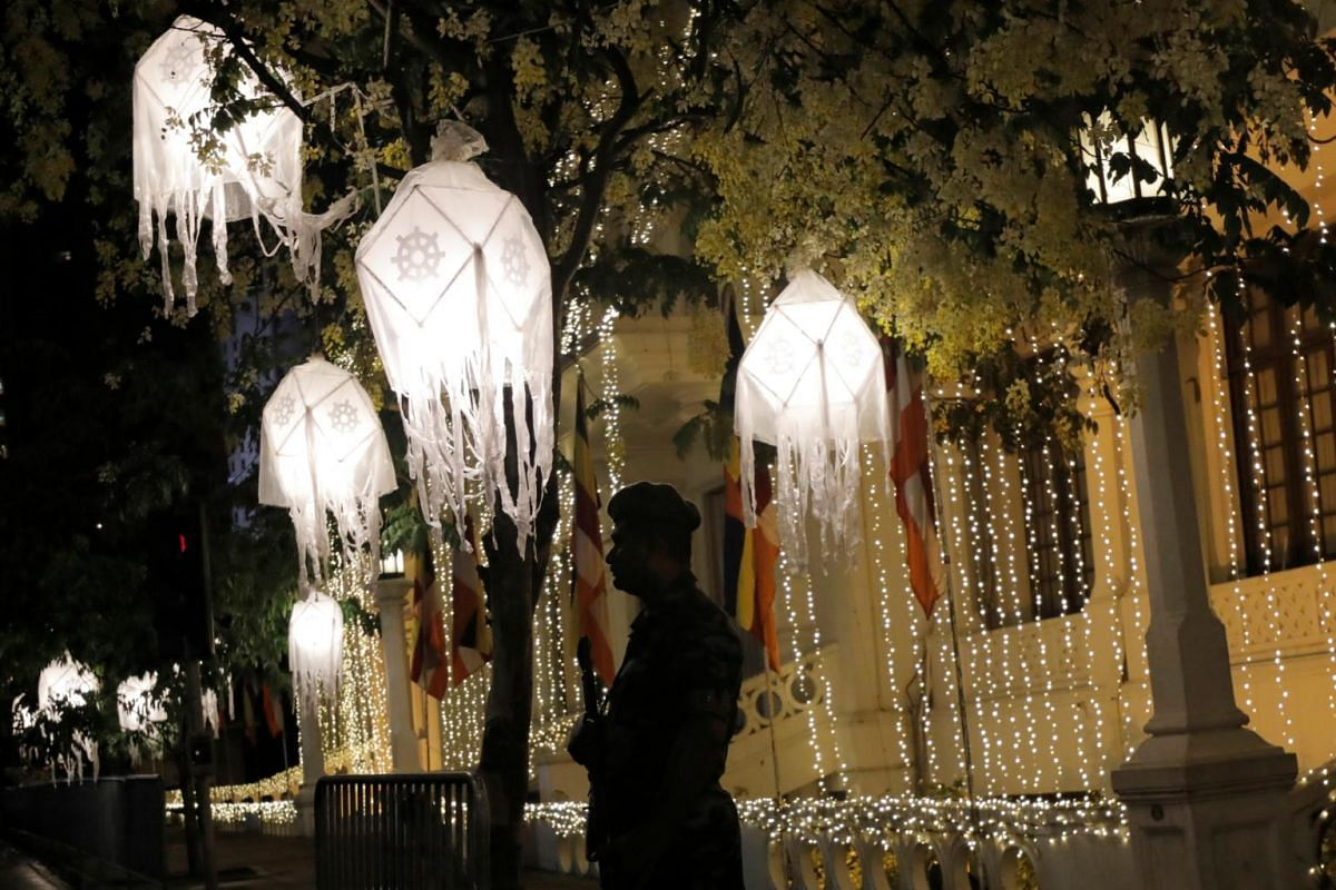 A military soldier stands guard near the main road decorated with lanterns during Vesak Day, in Colombo, Sri Lanka, on May 18, 2019.