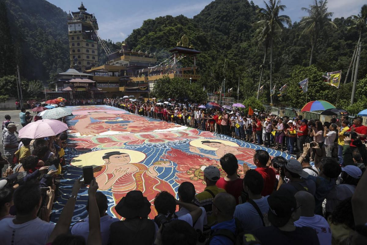 """A 60m by 12m """"thangka"""", a canvas painting of Buddha lays on the ground after it was carried by worshippers and unrolled during Vesak Day celebrations at the Enlightened Heart Tibetan Buddhist Temple in Perak, Malaysia, on May 19, 2019. It will then b"""