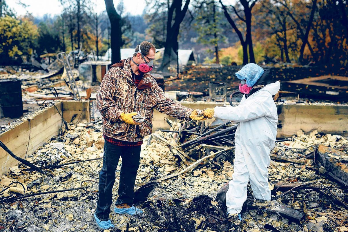 A couple inspecting the remains of their home in Paradise, California, after the so-called Camp Fire forced them to evacuate last November.