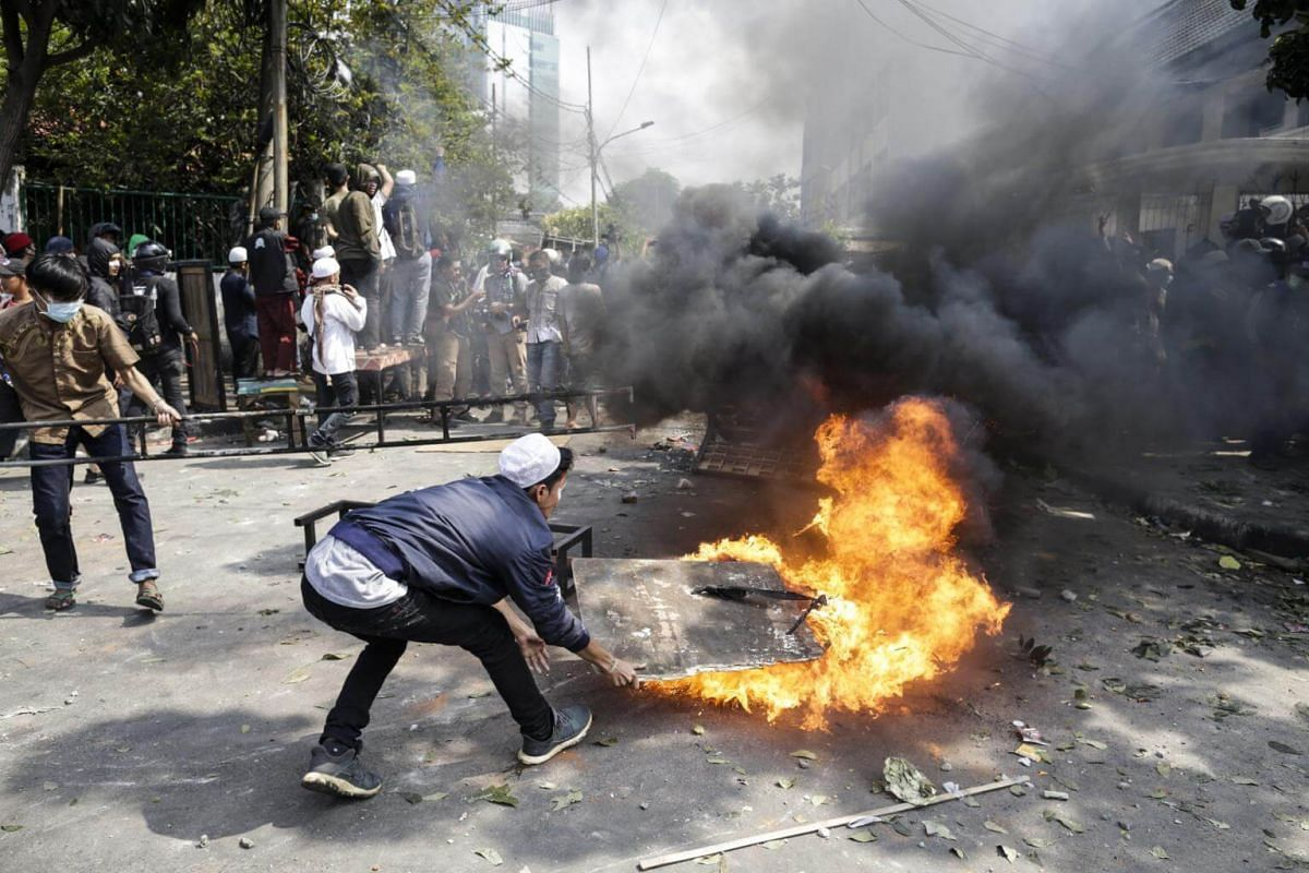 Indonesian protesters try to put out a fire from a burning tyre during a clash with riot police officers outside the election supervisory board building in Jakarta on May 22, 2019.