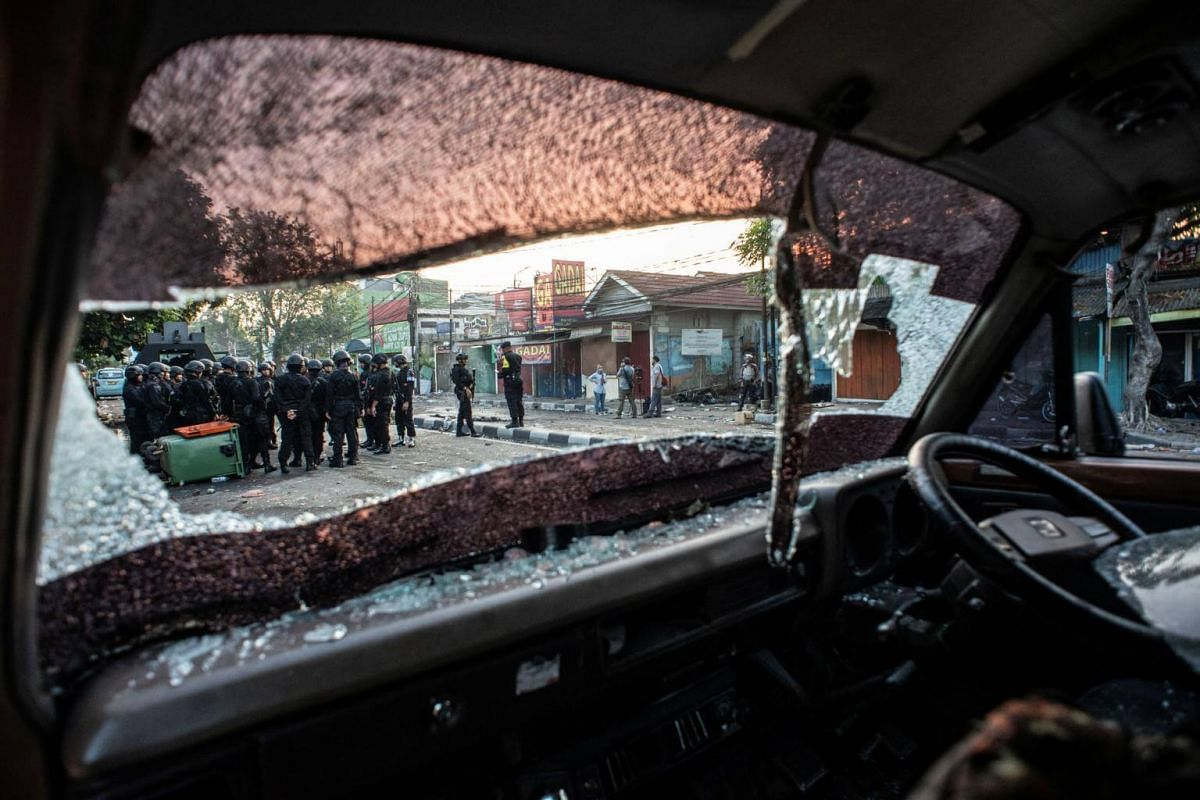Police are seen through a broken windscreen of a car after early morning clashes with protesters in Jakarta on May 22, 2019.