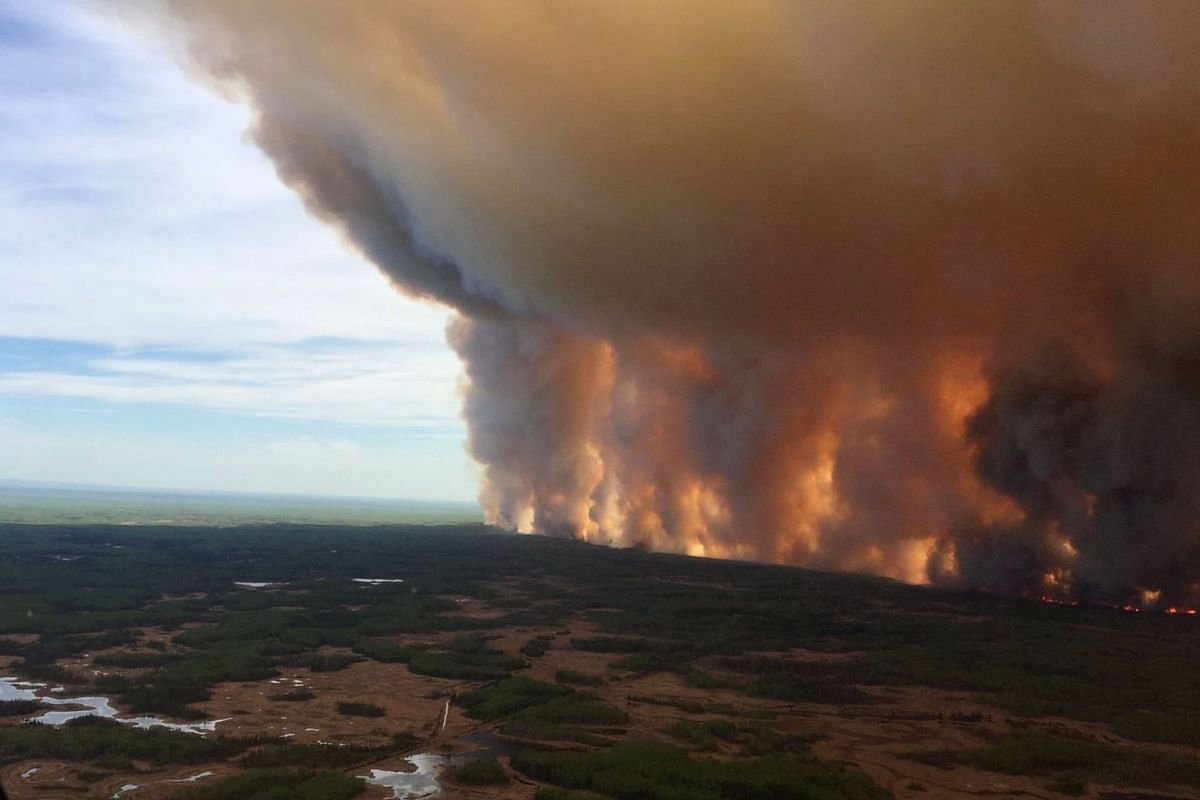 A handout photo made available by Alberta Wildfire on May 22, 2019, shows smoke rising from a wildfire in Chuckegg Creek, Southwest of High Level, Alberta, Canada, 19 May 2019 (Issued 22 May 2019). PHOTO: HANDOUT VIA EPA-EFE