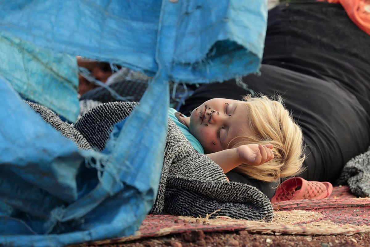 A photo released on May 23, 2019 shows a displaced Syrian child sleeping on a mat laid out on the floor in an olive grove in the town of Atmeh, Idlib province, Syria May 19, 2019. PHOTO: REUTERS