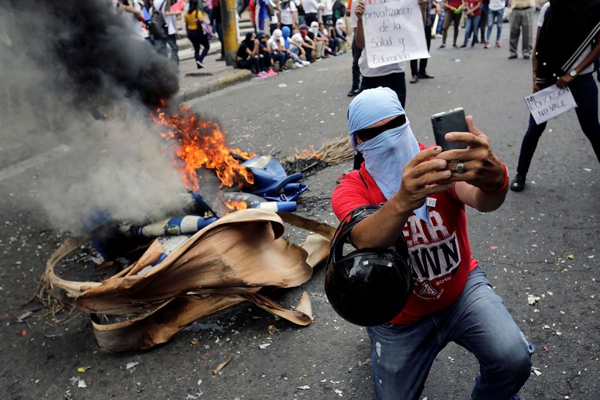 A demonstrator takes a selfie at a barricade during a protest against government plans to privatize healthcare and education, in Tegucigalpa, Honduras May 22, 2019. PHOTO: REUTERS
