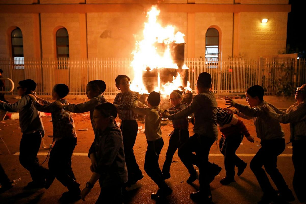 Ultra-Orthodox Jewish boys dance around a bonfire as they celebrate the Jewish holiday of Lag Ba'Omer in the city of Ashdod, Israel May 22, 2019. PHOTO: REUTERS