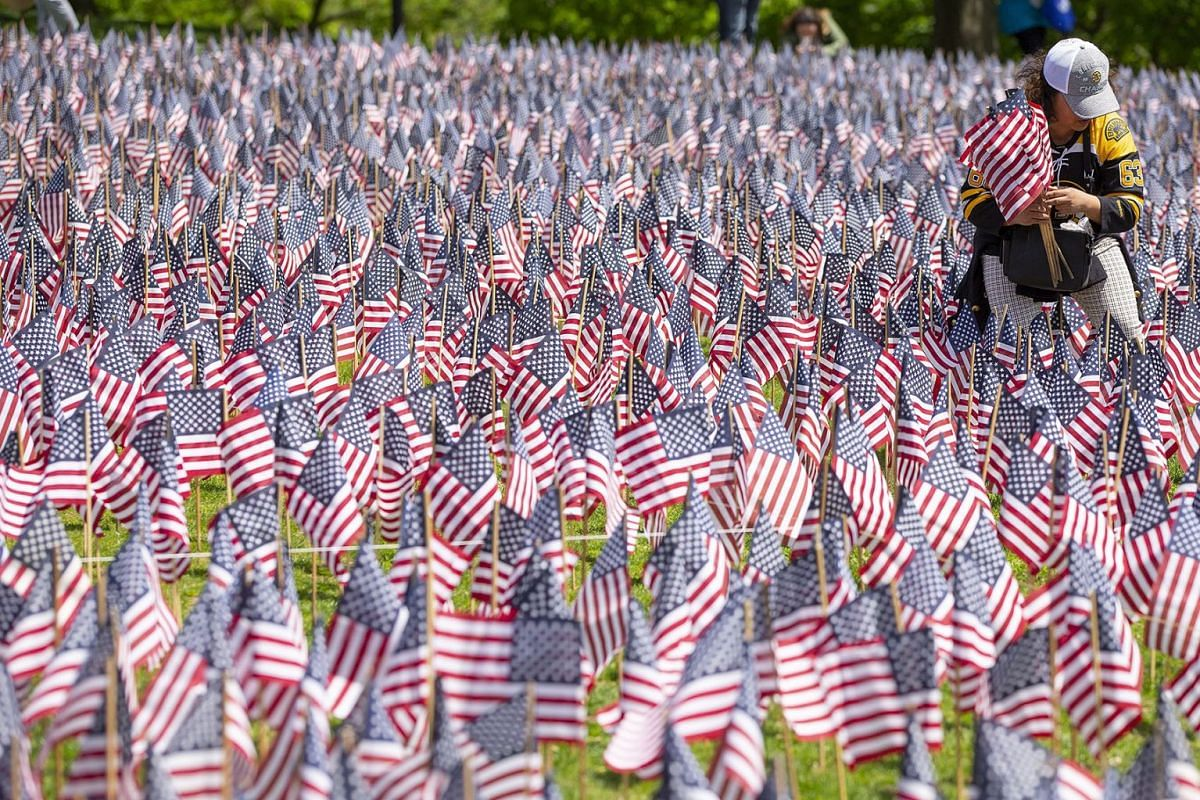 A volunteer helps place over 37,000 United States Flags on the Boston Common in preparation for the upcoming Memorial Holiday Weekend in Boston, Massachusetts, USA on May 22, 2019. PHOTO: EPA-EFE