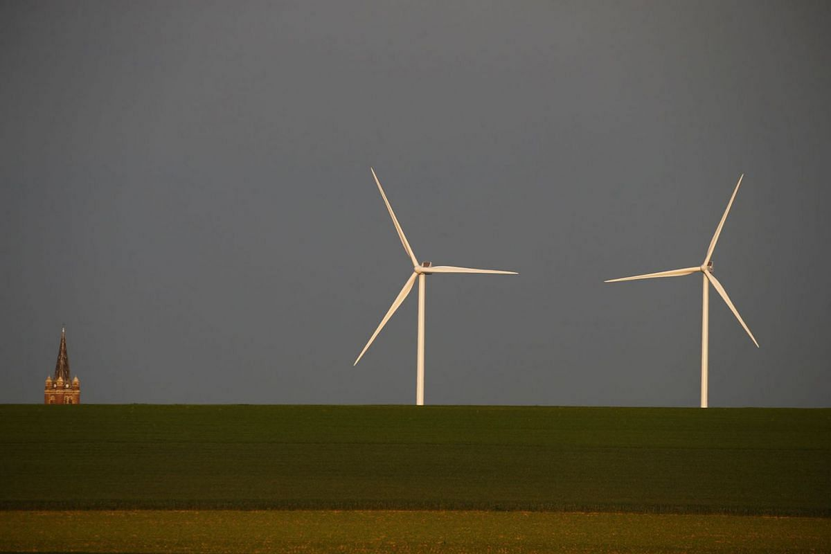 Two power-generating windmill turbines are seen beside the church steeple in Graincourt-les-Havrincourt, France May 22, 2019. PHOTO: REUTERS