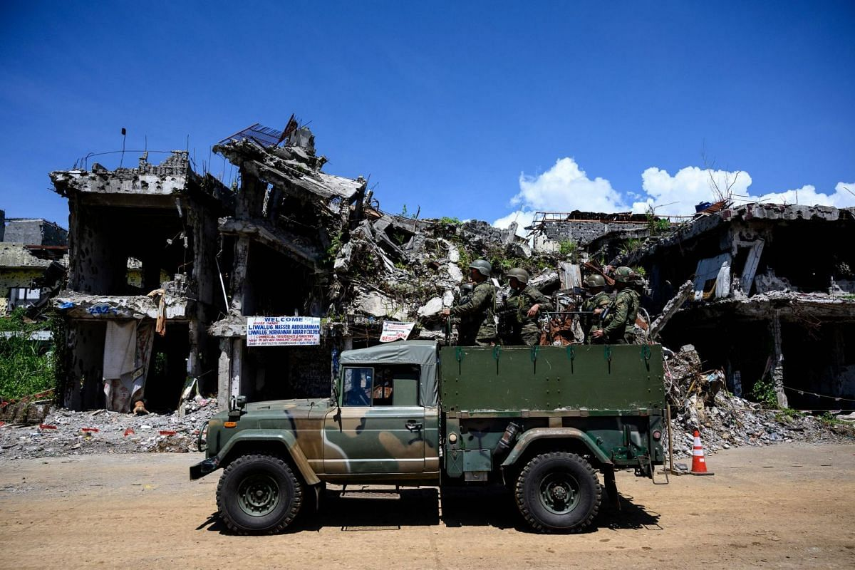 Soldiers riding on a military truck as they pass by a row of damaged buildings in Marawi.