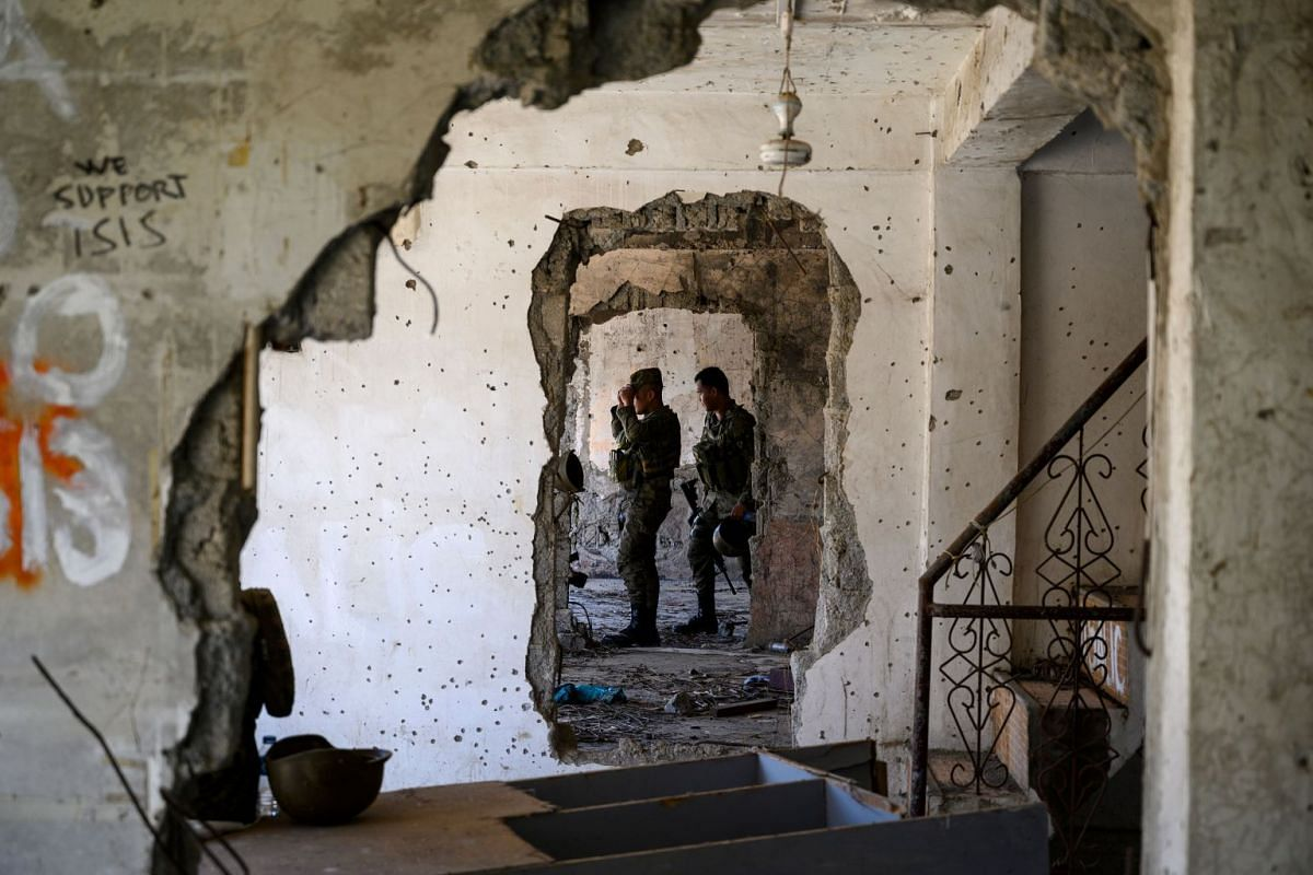 Soldiers walking through a damaged building in Marawi.