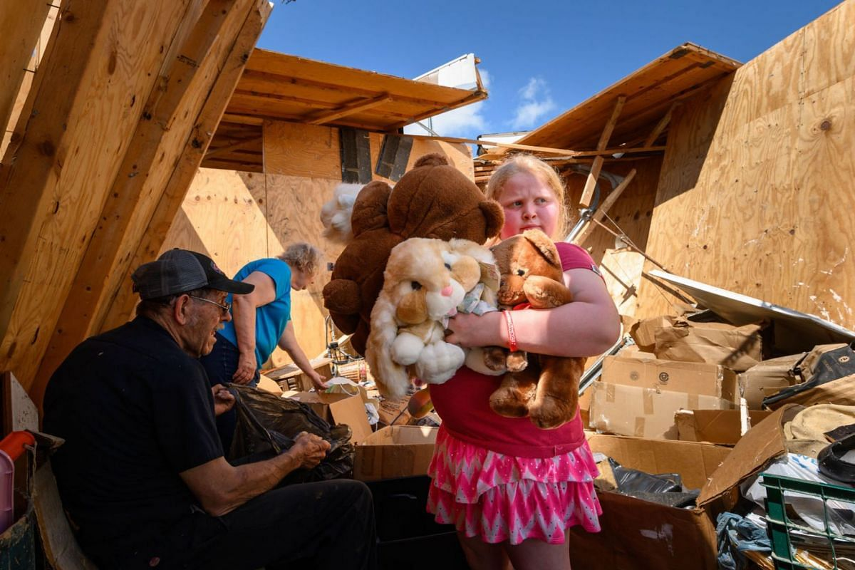 Nine-year-old Keeley Frank holds some stuffed animals her grandparents Al and Barb Scheidegger (at left) salvaged from their storage unit on May 23, 2019 in Jefferson City, Missouri. It was among many units destroyed by a tornado there on Thursday. P