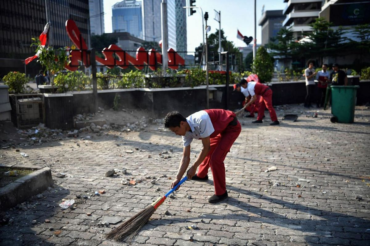 Workers cleaning up debris on May 23, 2019, after the previous night's violent clashes between police and rioters in Jakarta. PHOTO: THE STRAITS TIMES/ARIFFIN JAMAR