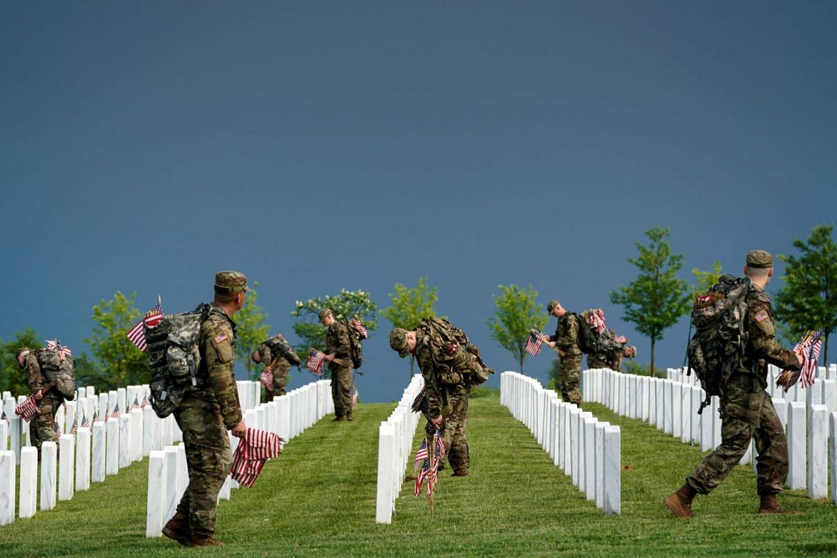 """Old Guard soldiers take part in """"Flags-In"""", an annual event where a small American flag is placed in front of more than 240,000 headstones of U.S. service members buried at Arlington National Cemetery in Arlington, Virginia, U.S., May 23, 2019. PHOTO"""