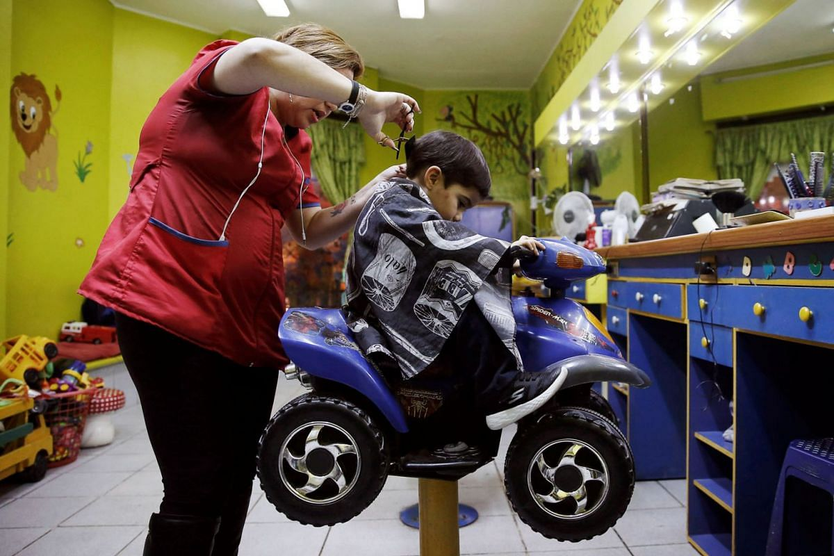 A child sits in a toy car as he gets his hair cut in a hairdressing salon for children in Vina del Mar, Chile, May 23, 2019. PHOTO: REUTERS