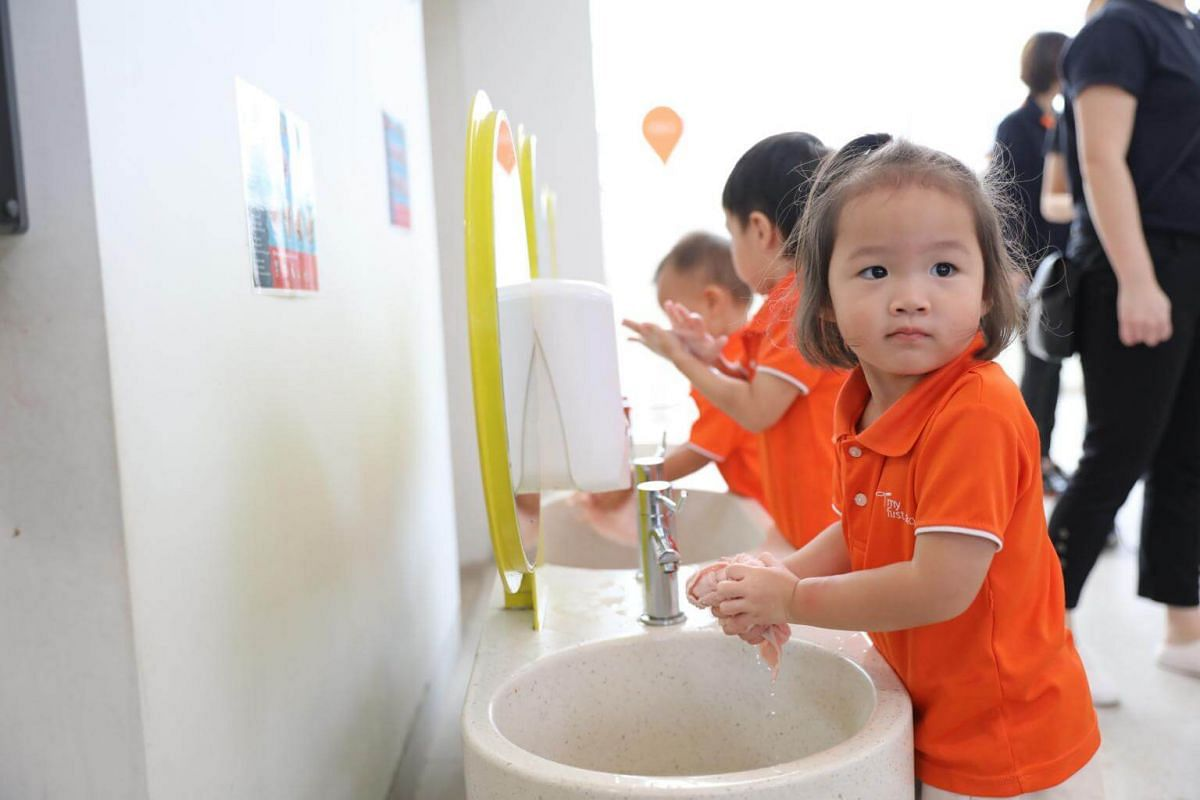 Three-year-old Kayla Xue wetting a wash cloth to wipe the table after her meal.
