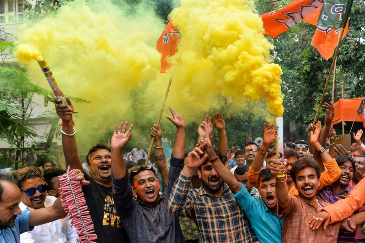 Indian supporters of Bharatiya Janata Party set off coloured smoke crackers as they celebrate the results of India's general election in Siliguri, on May 23, 2019.