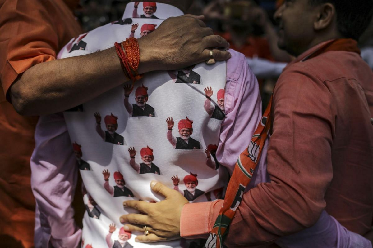 A supporter wears a waistcoat featuring images of India's Prime Minister Narendra Modi outside the Bharatiya Janata Party (BJP) state office in Mumbai, on May 23, 2019.