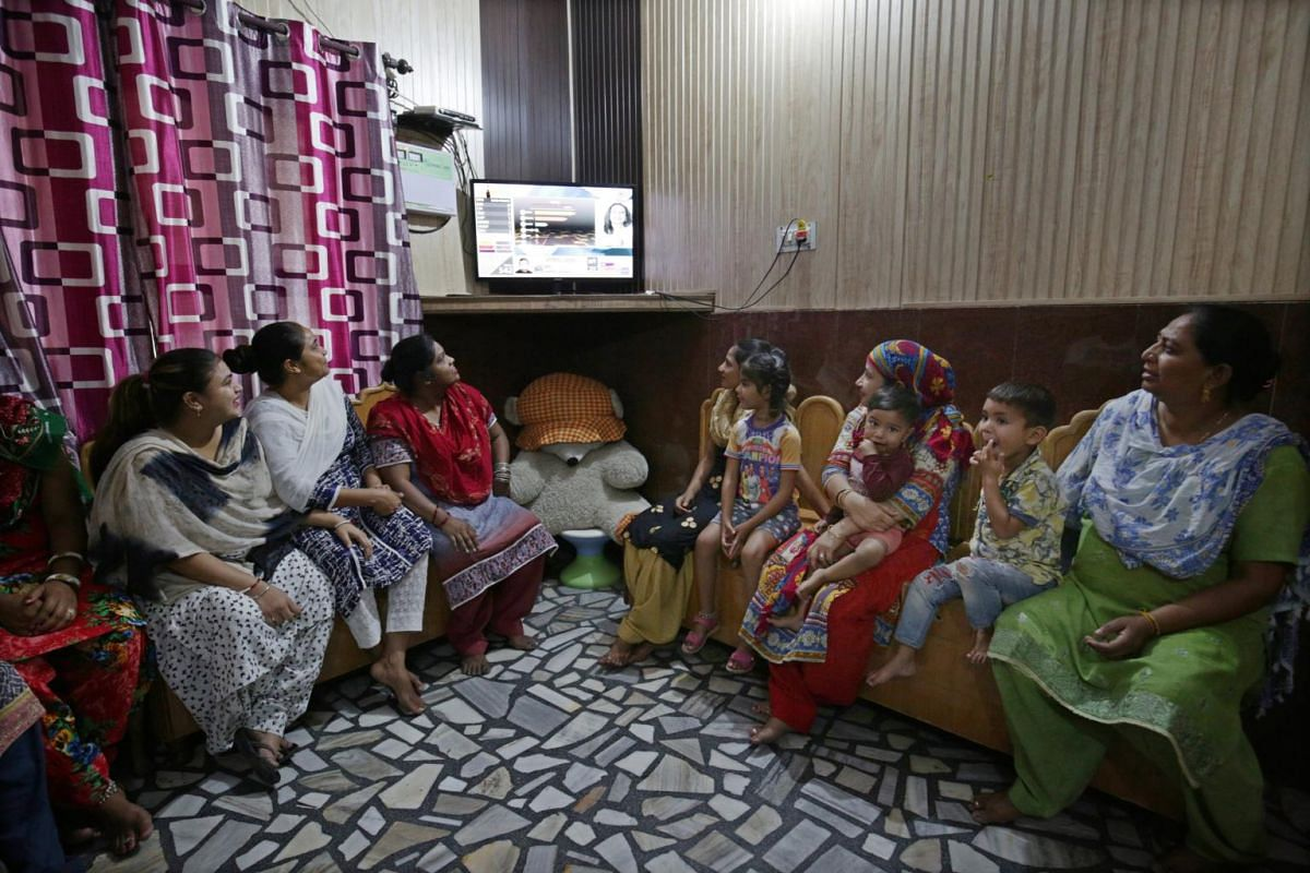 Indian women watch the Lok Sabha election results on a television screen in a slum area in Amritsar, on May 23, 2019.