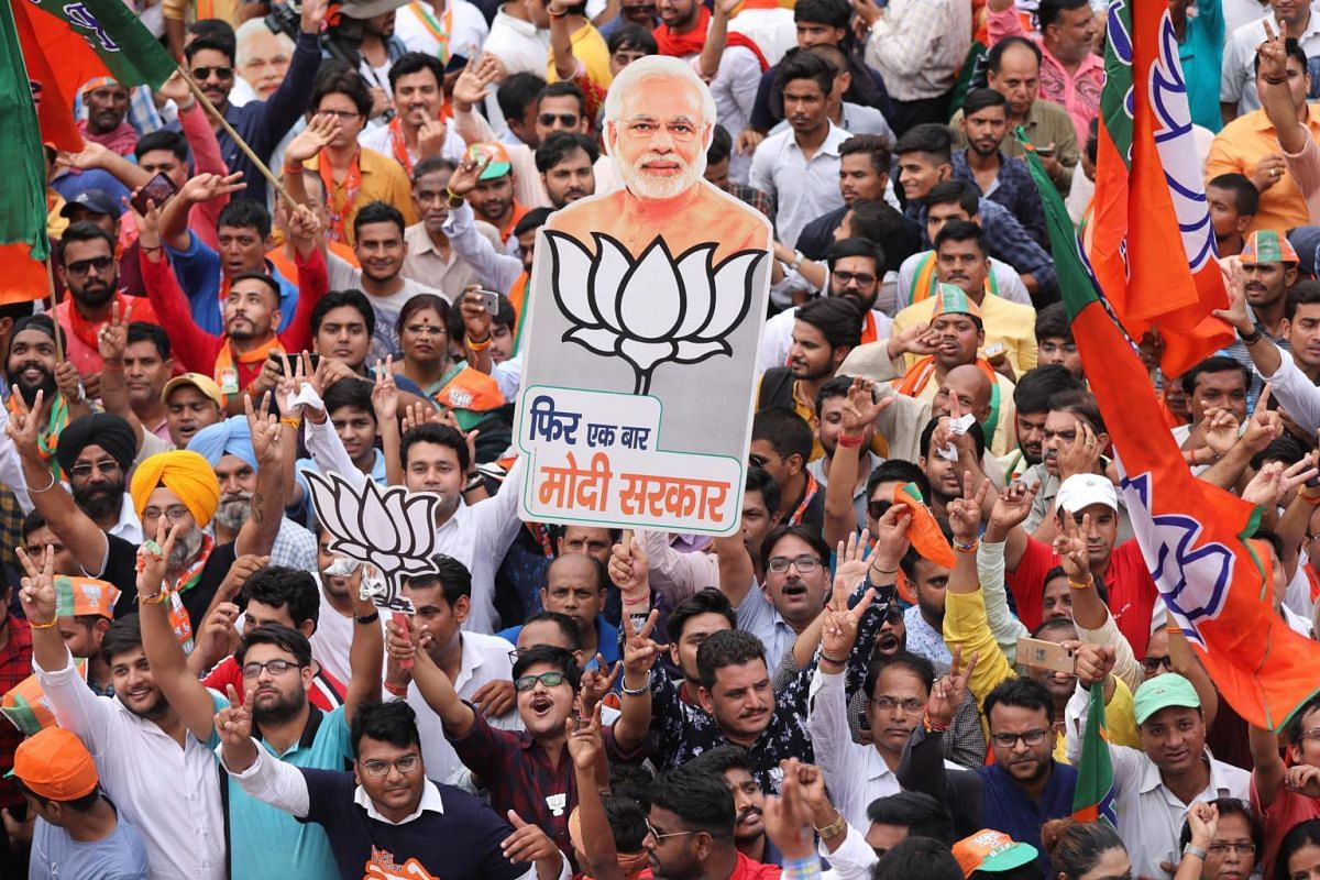 """Bharatiya Janata Party supporters hold placards that read in Hindi """"one more time Modi government"""" as they celebrate after the BJP's potential win in New Delhi, on May 23, 2019."""