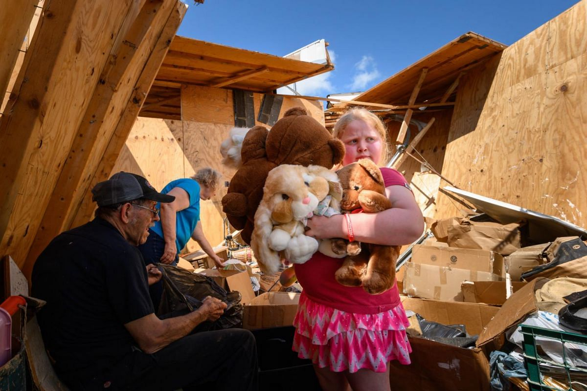 Nine-year-old Keeley Frank holds some stuffed animals her grandparents Al and Barb Scheidegger (at left) salvaged from their storage unit on May 23, 2019 in Jefferson City, Missouri.