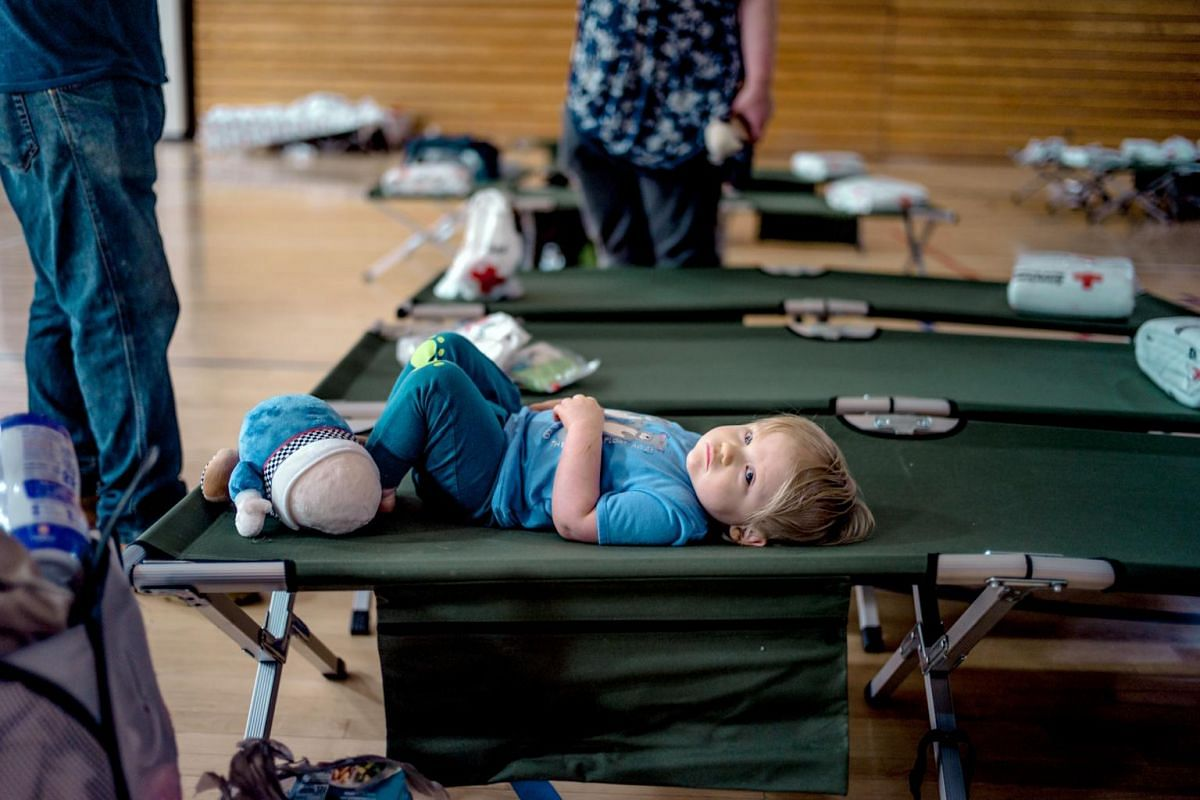 Theodore Trigo rests on a cot in an emergency shelter set up at Thomas Jefferson Middle School in Jefferson City, on May 23, 2019.