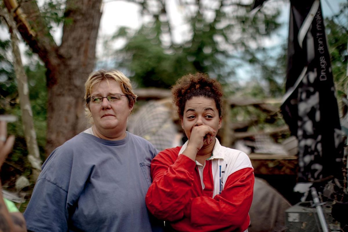 Tina Calderon (right) and a neighbour view the wreckage of their homes in Jefferson City, on May 23, 2019.