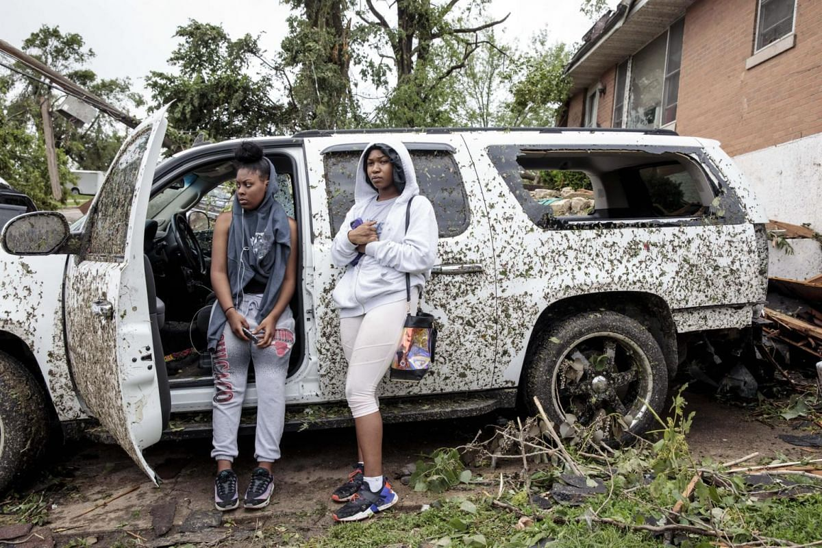 Tatianna Gordon (left), 16, and her cousin Tiera Brown, 17, prepare to leave after salvaging their belongings from the wreckage of Tiera's home in Jefferson City, on May 23, 2019.