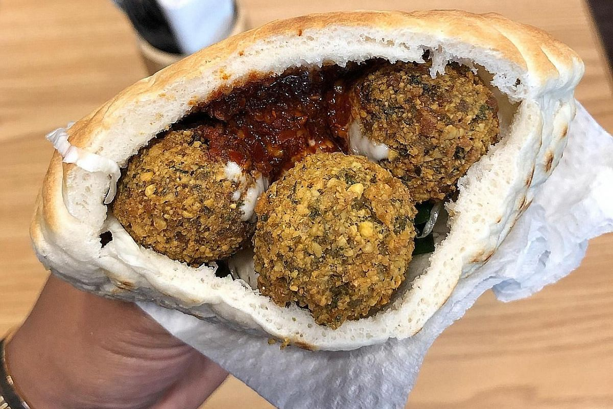 Pita pocket stuffed with falafel balls with pickled cabbage, tahini (ground, toasted sesame seeds) and harissa (hot chilli pepper paste).