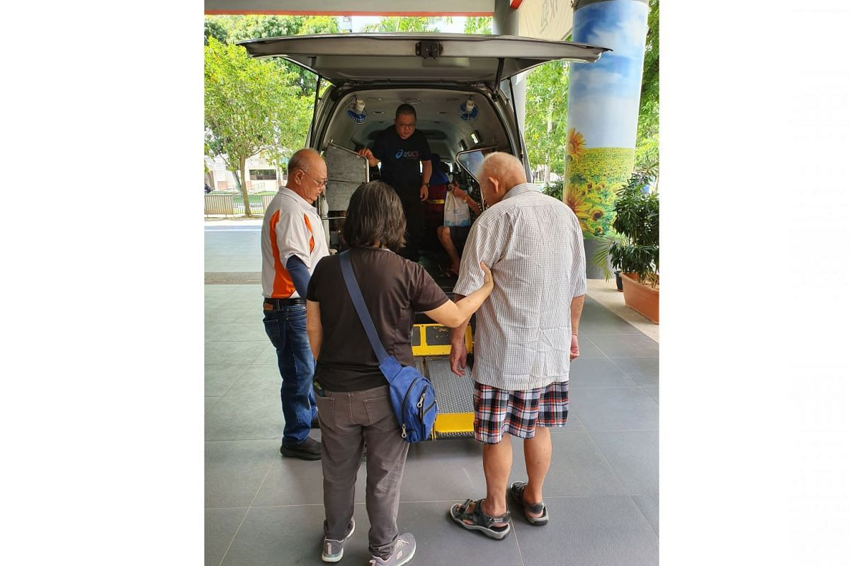 Mr Teng Seng Chye (in beige shirt), being helped by staff members from Awwa. He lives alone in a two-room rental flat in Whampoa and goes to a dementia day care service run by the Tsao Foundation at the Whampoa Community Club.