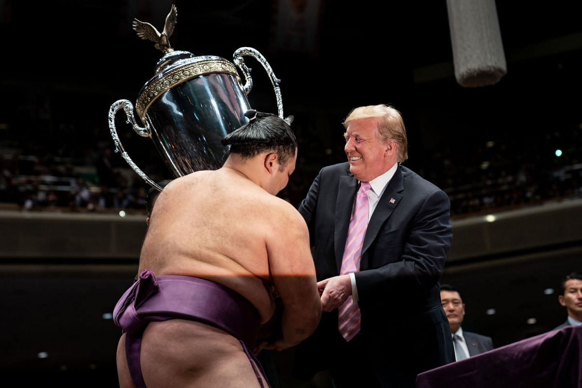 President Donald Trump presents the President's Cup to the Tokyo Grand Sumo Tournament winner Asanoyama, at Ryogoku Kokugikan Stadium in Tokyo, on May 26, 2019. PHOTO: THE NEW YORK TIMES