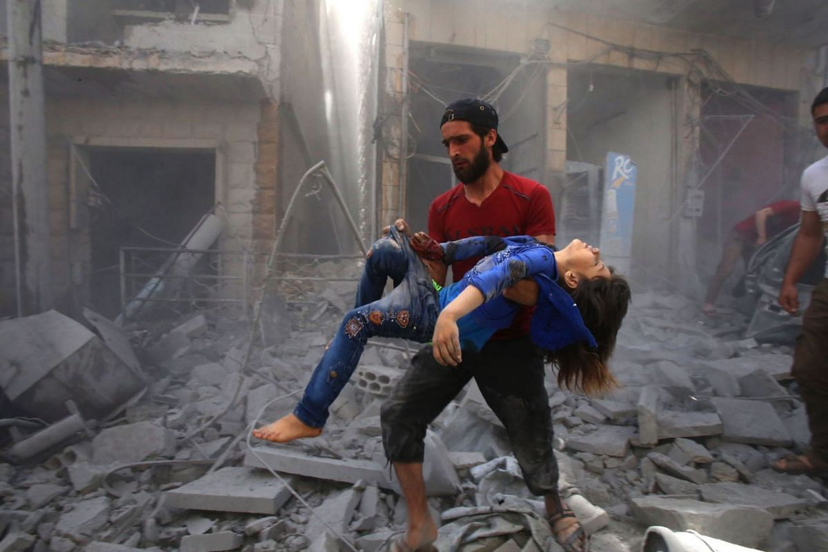 A man evacuates a young bombing casualty after a reported air strike by regime forces and their allies in the jihadist-held Syrian town of Maaret Al-Noman in the southern Idlib province, on May 26, 2019. PHOTO: AFP