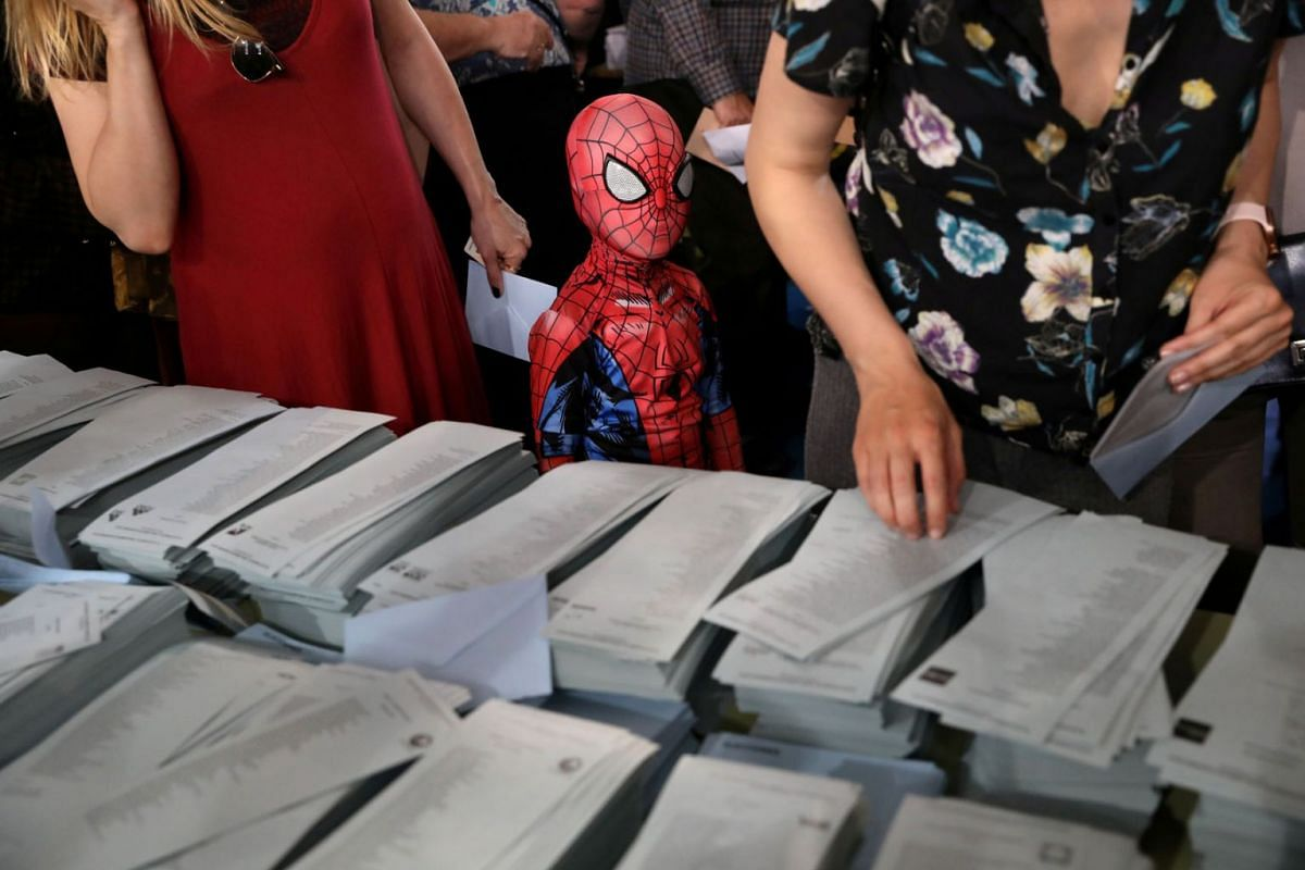 A kid in a Spiderman costume stands next to a ballot table for the European Parliament election at a polling station in Madrid, Spain, May 26, 2019. PHOTO: REUTERS