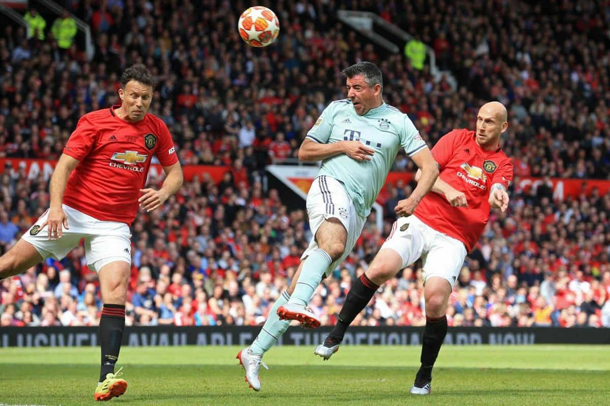 Manchester United '99 Legends' Ronny Johnsen (left) and Jaap Stam watch as FC Bayern Legends' striker Roy Makaay wins a header during the Treble Reunion 20th anniversary football match at Old Trafford, on May 26, 2019.
