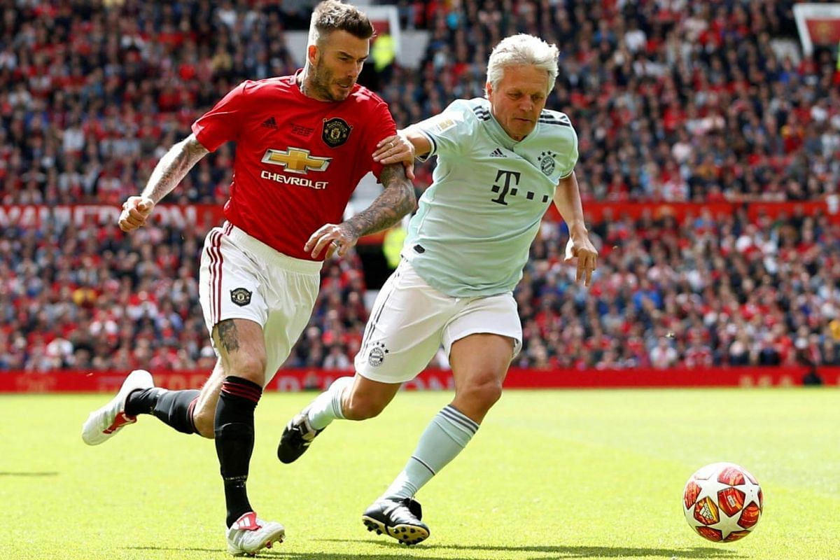 Manchester United '99 Legends' David Beckham in action against FC Bayern Legends' Stefan Effenberg during the Treble Reunion 20th anniversary football match at Old Trafford, on May 26, 2019.
