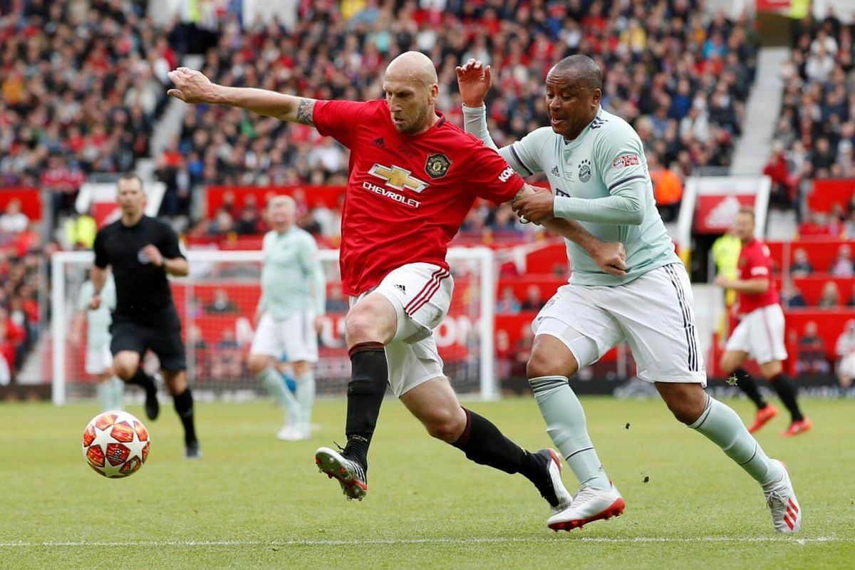 Manchester United '99 Legends' Jaap Stam in action against FC Bayern Legends' Paulo Sergio during the Treble Reunion 20th anniversary football match at Old Trafford, on May 26, 2019.
