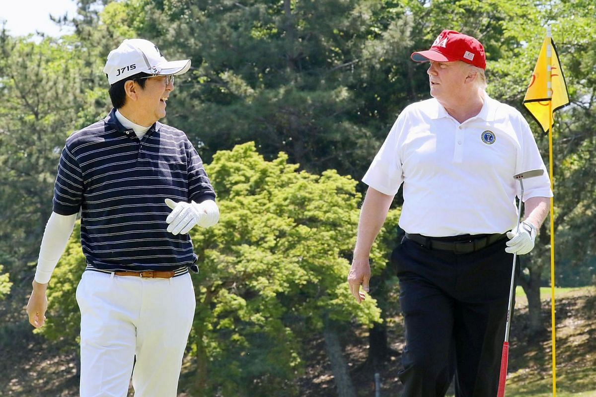 US President Donald Trump talks with Japanese Prime Minister Shinzo Abe as they play golf at Mobara Country Club in Mobara, Chiba prefecture, Japan on May 26, 2019.