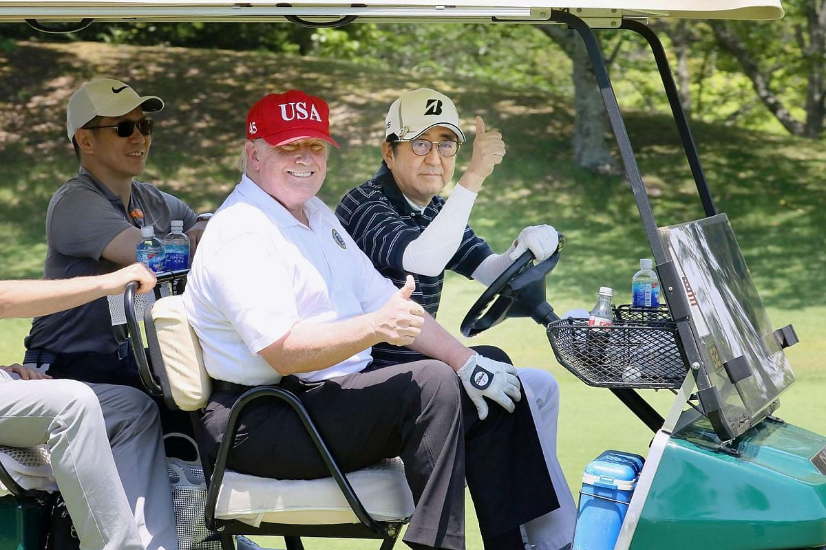 US President Donald Trump sits on a cart with Japanese Prime Minister Shinzo Abe driving as they play golf at Mobara Country Club in Mobara, Chiba prefecture, Japan on May 26, 2019.