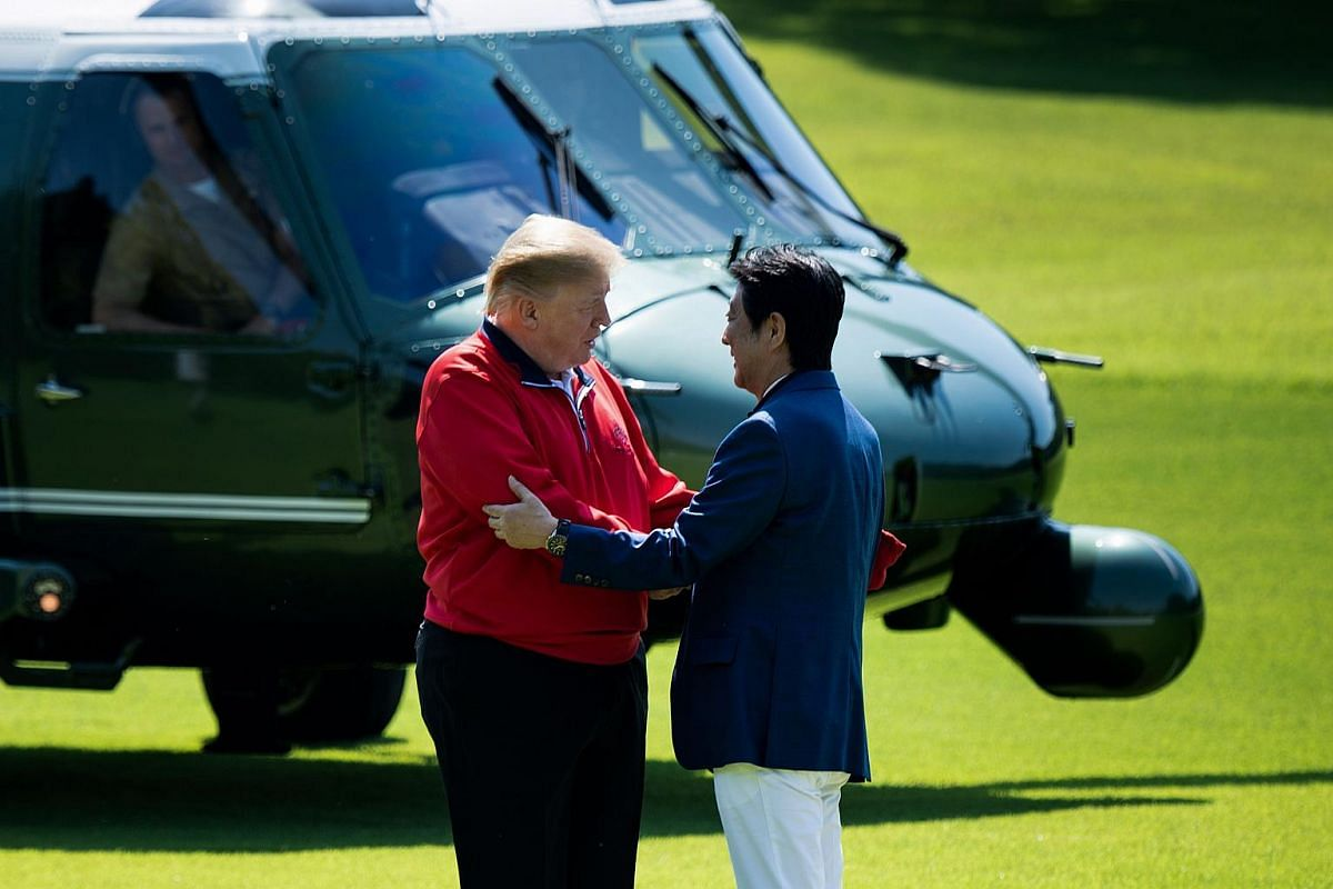 Japanese Prime Minister Shinzo Abe greets US President Donald Trump before playing a round of golf at Mobara Country Club in Chiba on May 26, 2019.