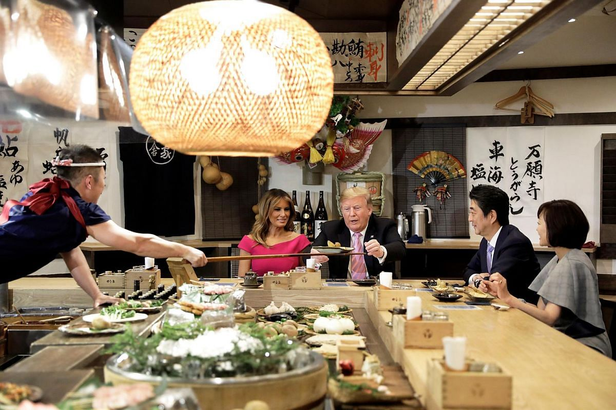 US President Donald Trump, with first lady Melania Trump, receives a plate of food from a chef as they and Japanese Prime Minister Shinzo Abe and his wife Akie Abe have a couples dinner in Tokyo, Japan on May 26, 2019.